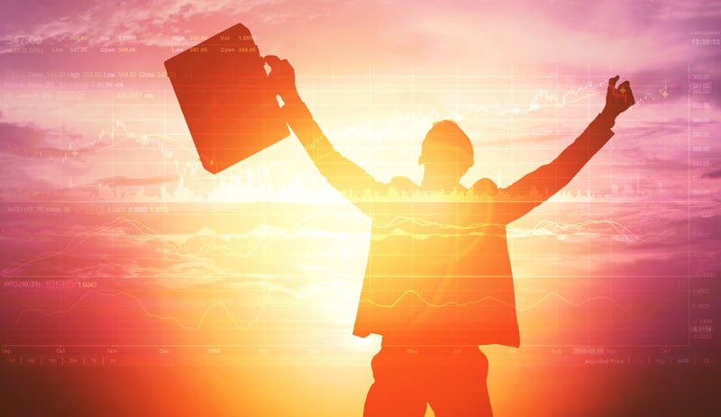 A forex trader raising his arms in joy with a beautiful sunrise behind him.